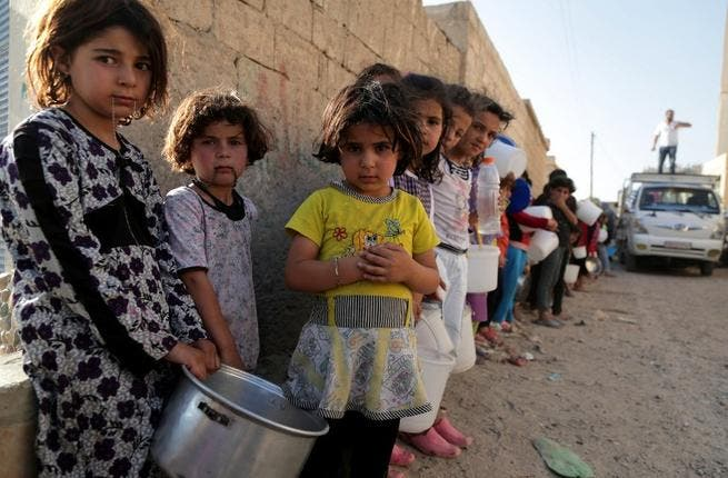 """SYRIA, RAQQA : Syrian children wait in line to collect a free """"Iftar"""" meal in the northern city of Raqqa during the Muslim holy month of Ramadan on July 14, 2013. (AFP PHOTO/MEZAR MATAR)"""