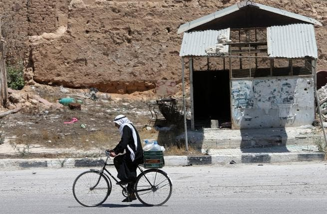 SYRIA, QUSAYR : A Syrian resident rides his bicycle on August 1, 2013 in a street of the city of Qusayr, in Syria's central Homs province. AFP PHOTO/JOSEPH EID