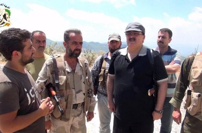 SYRIA, Latakia : An image grab taken from a video published on the Youtube account Jableh1990 on August 11, 2013 allegedly shows Syrian rebel leader General Salim Idris (C-R) talking to rebel fighters in the outskirts of Latakia.  AFP PHOTO/YOUTUBE