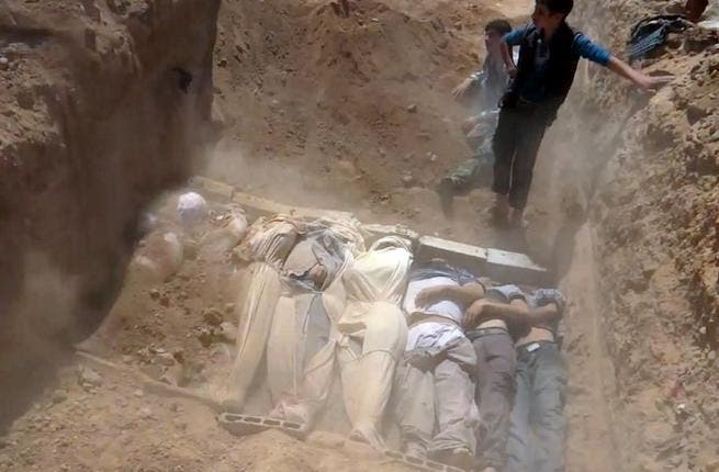 SYRIA, DAMASCUS : An image grab taken from a video uploaded on YouTube by the Local Committee of Arbeen on August 21, 2013 allegedly shows Syrians covering a mass grave containing bodies of victims that Syrian rebels claim were killed in a toxic gas attack by pro-government forces in eastern Ghouta and Zamalka, on the outskirts of Damascus. AFP PHOTO / YOUTUBE / LOCAL COMMITTEE OF ARBEEN