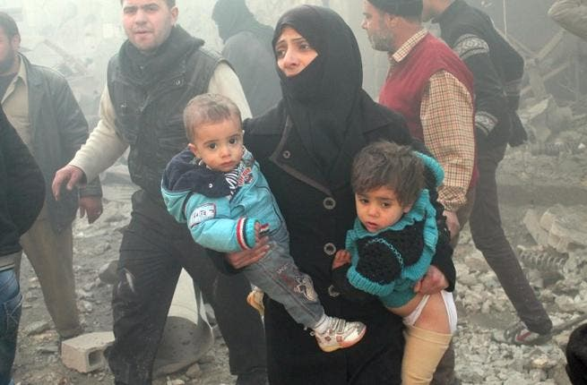 A Syrian woman carries children following airstrikes on a rebel area of the war-torn northern city of Aleppo on December 15, 2013. [AFP]