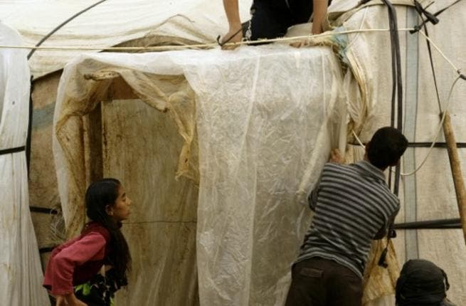 A Syrian refugee family covers their make shift home with plastic sheeting as a rain and cold weather front envelops the region, close to the southern Lebanese village of Sardah on December 29, 2013. [AFP]