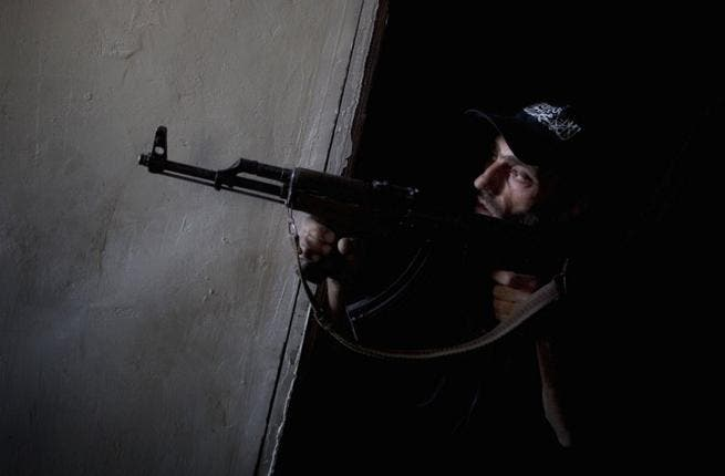 Syrian opposition fighter peers around a corner with weapon (AFP)
