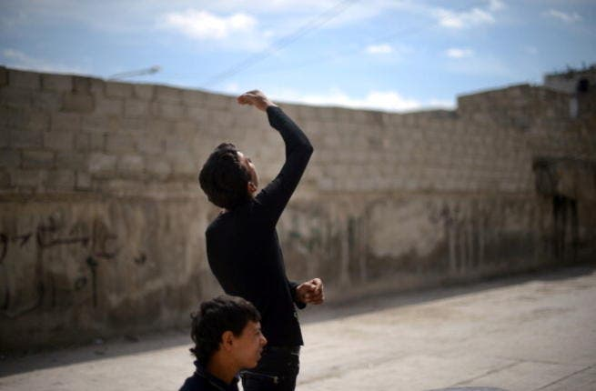 A Syrian young man looks up as a government forces fighter jet flies overhead in the northern Syrian city of Aleppo on April 15, 2013. ( DIMITAR DILKOFF/AFP/Getty Images)