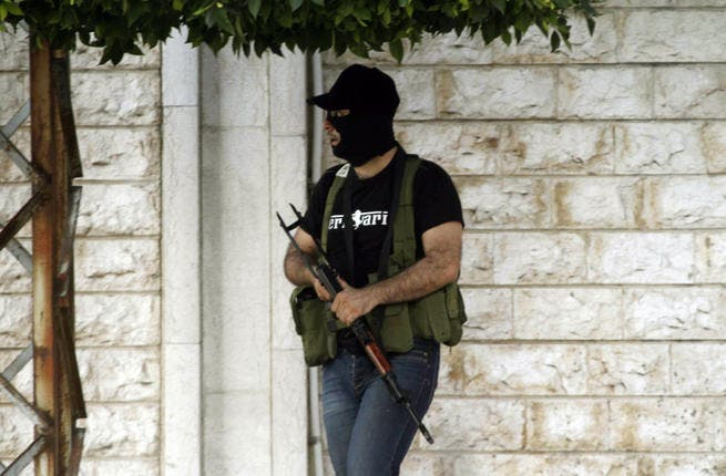 A masked gunman opposed to the Shiite party Hezbollah, stands in the southern town of Sidon's eastern suburb of Abra, on June 18, 2013. (File photo / AFP)