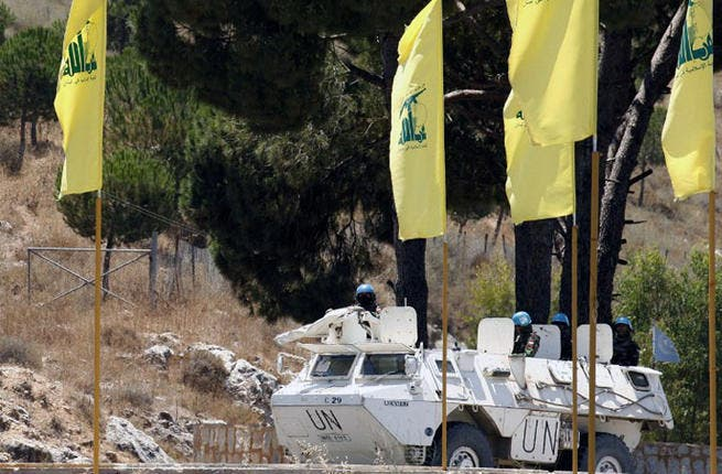LEBANON, MARJAYOUN : Spanish peacekeepers of the United Nations Interim Force in Lebanon (UNIFIL) patrol in their armoured vehicles near a placard of Hezbollah on July 23, 2013 in the southern Lebanese city of Marjayoun. AFP PHOTO MAHMOUD ZAYYAT