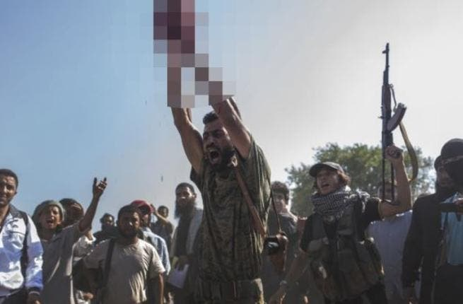 An ISIS soldier, in a recent execution, holds the severed head of a militant. [LeJournal]