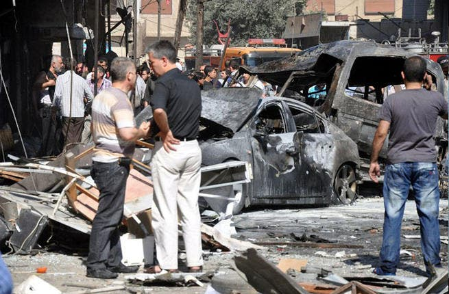 SYRIA, DAMASCUS : A handout picture released by the Syrian Arab News Agency (SANA) shows Syrians looking at burned-out car bombs after an attack that at least killed seven people and wounded 62 on July 25, 2013 in Jaramana suburb in southeast Damascus. AFP PHOTO / HO / SANA