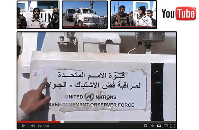 An image grab taken from a video uploaded on YouTube on Wednesday, allegedly shows armed fighters standing in front of a United Nations Disengagement Force (UNDOF) vehicle in the Golan Heights between Syria and Israel. (Image courtesy of AFP / YouTube)