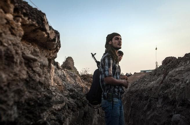 SYRIA, DERIK : Fighters of the Kurdish of the Committees for the Protection of the Kurdish People (YPG) stand in a trench on August 28, 2013 about 30 kms south of the Kurdish town of Derik (aka al-Malikiyah in Arabic), in northeastern Hasakeh governorate, on the border with Turkey and Iraq. AFP PHOTO ALICE MARTINS