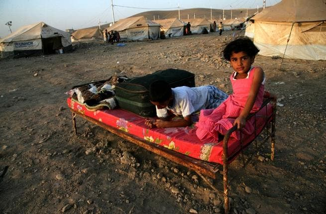 IRAQ, Arbil : A Syrian-Kurdish children sitting on a bed at the Quru Gusik refugee camp, 20 kilometres east of the of Arbil, the capital of the autonomous Kurdish region of northern Iraq, on August 22, 2013. TOPSHOTS/AFP PHOTO/SAFIN HAMED