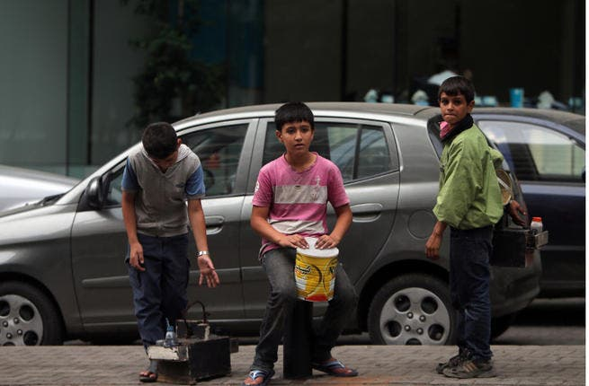 Young Syrian refugees carrying shoe shine kits as they search for customers in a street in Beirutt. Seven million people are in urgent need of humanitarian aid due to the conflict in Syria, a UN top official said. (Image credit: AFP)