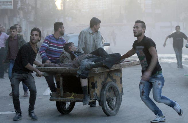 Two injured men are transported on a fruit barrow in the Syria, following a shelling. (Image credit: AFP)