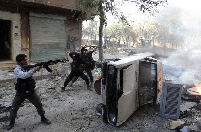 Opposition fighters open fire taking cover from behind a car during fightings in the Salaheddin district of the northern Syrian city of Aleppo  (Image credit: AFP)