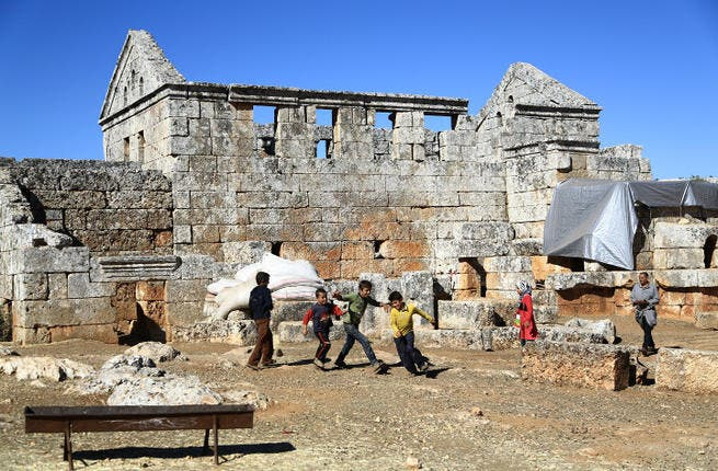 Syrian refugee children play in front of the ruins of the public baths of the ancient Byzantine-Christian city of Serjilla. (Image credit: AFP)