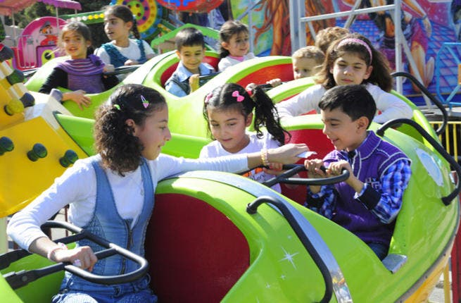 Syrian children ride on a merry-go-round as families celebrate the Muslim feast of Eid al-Adha. (Image credit: AFP)