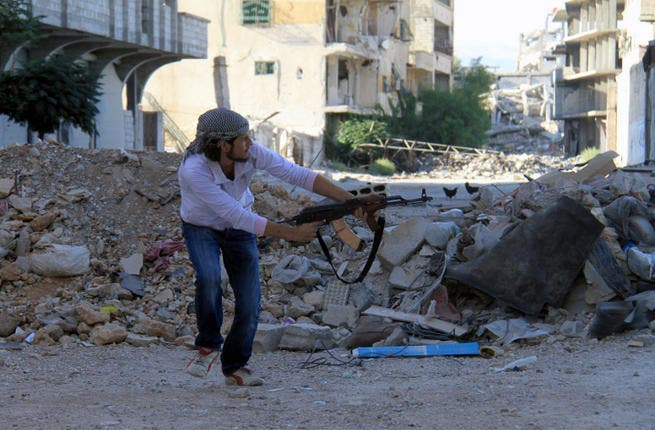 """A rebel fires a gun in Syria. Women have appeared on Syrian television saying they were kidnapped by rebel forces for """"sexual jihad."""" (Image credit: AFP)"""