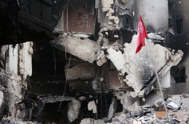 Rebel fighters walk in the rubble of destroyed building in Syria. (Image credit: AFP)