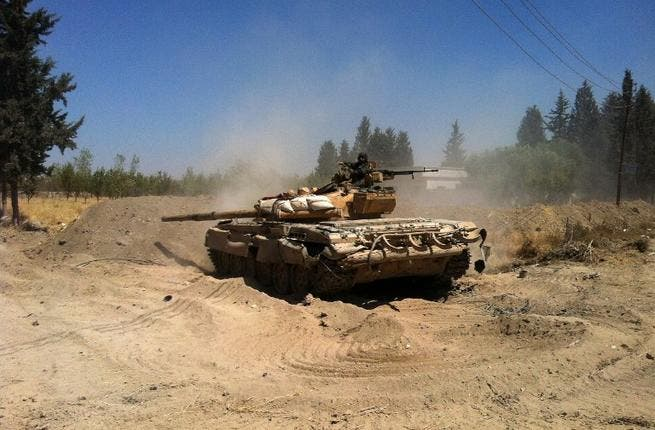 SYRIA, DAMASCUS : A Syrian army tank maneuvers in the Eastern Ghouta area on the northeastern outskirts of Damascus on August 30, 2013. AFP PHOTO/SAM SKAINE