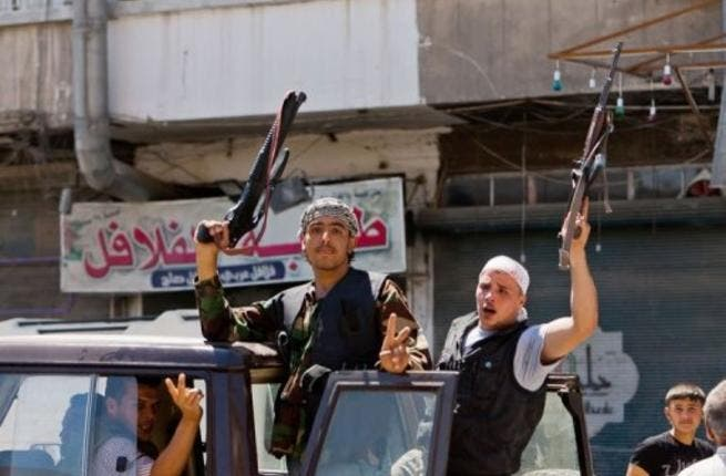 Syrian rebels hold their weapons aloft