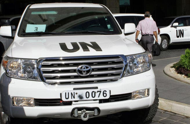 United Nations vehicles are seen leaving the hotel in Damascus on October 3, 2013. (Image credit: AFP)