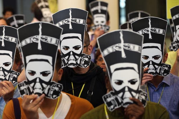 Delegates at a meeting of Amnesty International hold up masks depicting ancient Egyptian Queen Nefertiti wearing a gas mask in protest against the ongoing violence as well as sexual violence against women in Egypt on August 19, 2013. [ Getty Images]