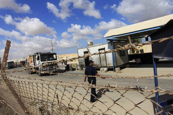 Trucks cross into Rafah town through the Kerem Shalom crossing between Israel and the southern Gaza Strip. [Said Khatib/AFP]