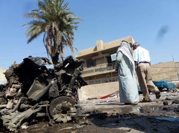 Iraqis look at the remains of a vehicle following an explosion on October 27, 2013, in the the Mashtal district of the capital Baghdad. [SABAH ARAR/AFP/Getty Images]
