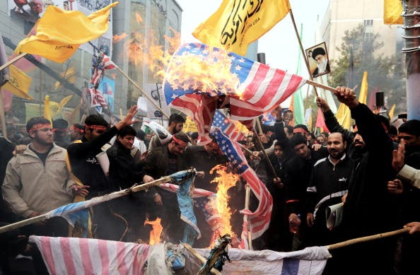 Iranians burn US flags outside the former US embassy in Tehran on November 4, 2013, during a demonstration to mark the 34th anniversary of the 1979 US embassy takeover. [Getty Images]