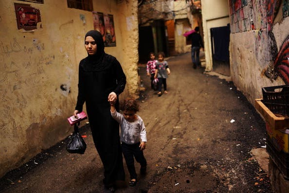 A Syrian woman displaced by the war walks with her child in a neighborhood with a high concentration of Syrian refugees on November 9, 2013 in Beirut, Lebanon.  [Spencer Platt/Getty Images]