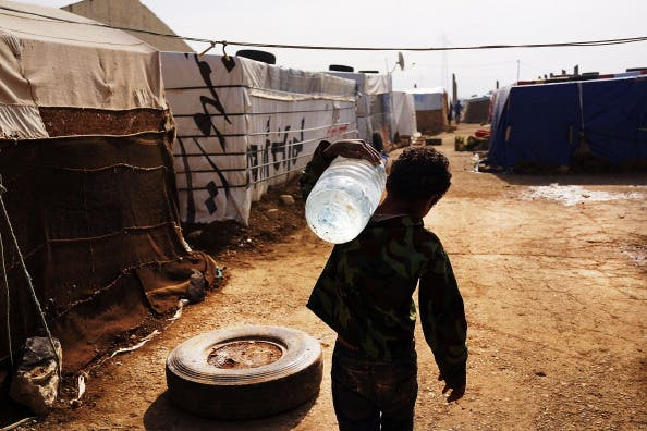 A displaced Syrian child walks through a camp with a jug of water in a makeshift camp for Syrian refugees only miles from the border with Syria in the Bekaa Valley on November 12, 2013 in Majdal Anjar, Lebanon. [Spencer Platt/ Getty Images]