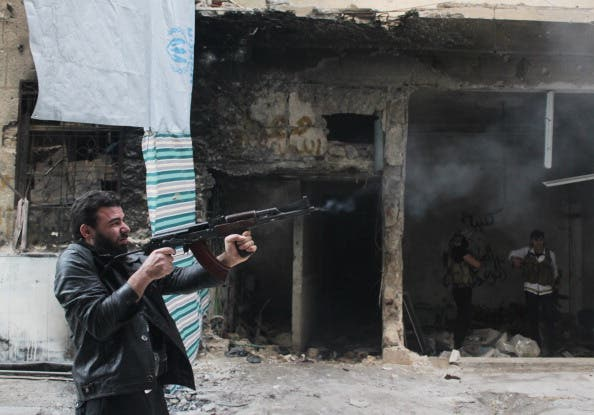 A rebel fighter from the Free Syrian Army fires his weapon during fighting against government forces on November 18, 2013. [Getty Images]