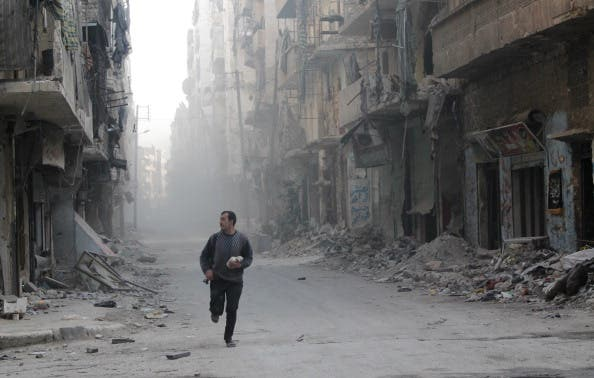 A rebel fighter from the Free Syrian Army runs in a street of Aleppo's Salah al-Din neighbourhood during fighting against Syrian government forces on November 18, 2013. [AFP]