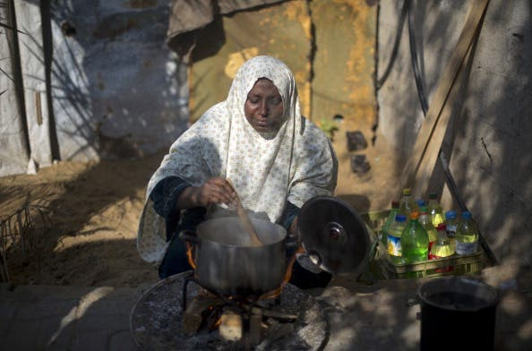 A Palestinian woman cooks her food on fire wood in Biet Hanun northern Gaza Strip, on November 19, 2013, due to the shortage in butane gas across the Hamas run Palestinian territory. [AFP]