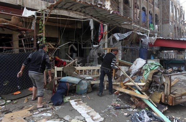 Iraqi men clean the rubble at the site of a blast that took place the previous day outside a cafe in Baghdad's Bayaa neighborhood on November 21, 2013. [Getty Images]