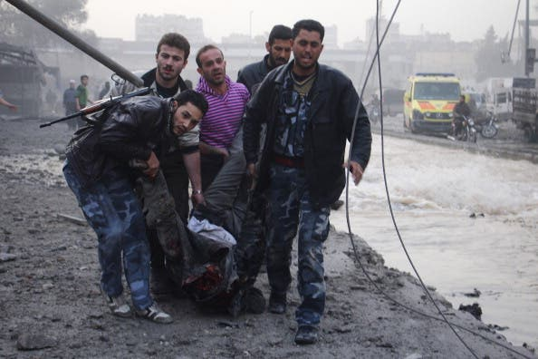 Rebels and civilians carry the body of a man killed after an air strike by pro-government forces on the Syrian city of Aleppo on November 28, 2013. [AFP]