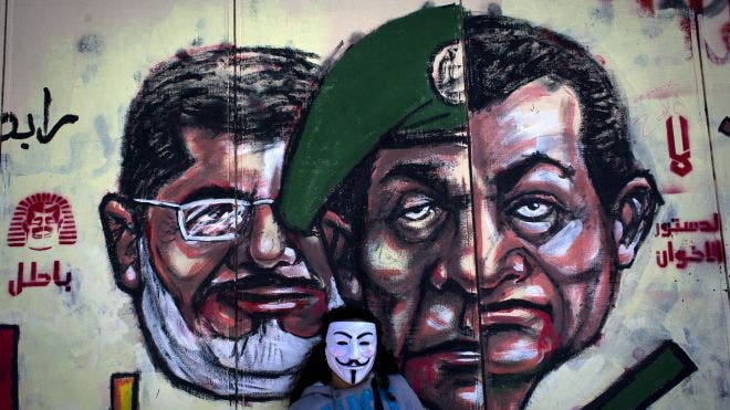 Egyptian protester wears a Guy Fawkes mask while posing for a photo next to a mural painted overnight on the exterior wall of the presidential palace depicting president Mohammed Morsi, left, former military council ruler Hussein Tantawi, center and ousted President Mubarak with Arabic that reads