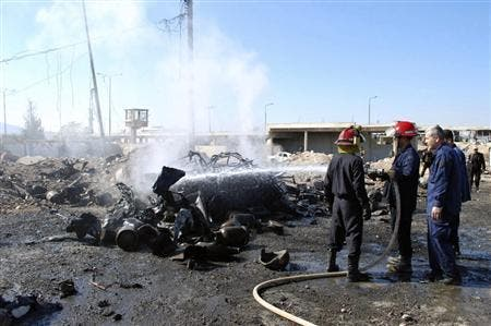 Fire-fighters extinguish a vehicle on fire after a suicide bomber in a truck carried out an attack at the eastern entrance of Hama city ,October 20, 2013. [Reuters/SANA/Handout]