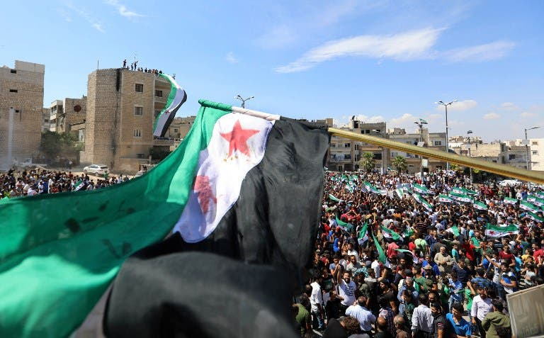 Syrian protesters wave the flag of the opposition as they demonstrate against the regime and its ally Russia, in the rebel-held city of Idlib on September 7, 2018. (OMAR HAJ KADOUR / AFP)