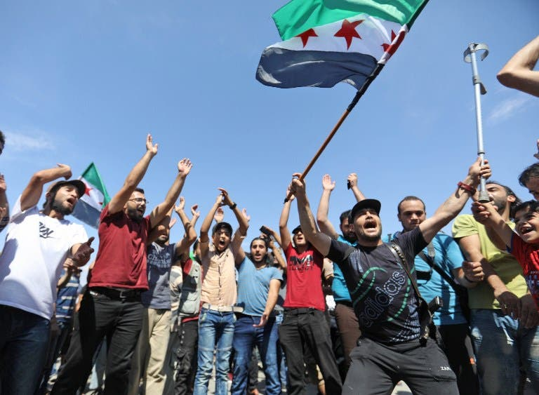 Syrian protesters wave the flag of the opposition as they demonstrate against the regime and its ally Russia, in the rebel-held city of Idlib on September 7, 2018.(OMAR HAJ KADOUR / AFP)