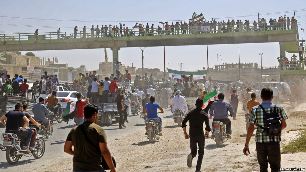 Syrians chant slogans and wave flags of the opposition as they protest against a promised government assault on Idlib province. (Zein Al RIFAI / AFP)