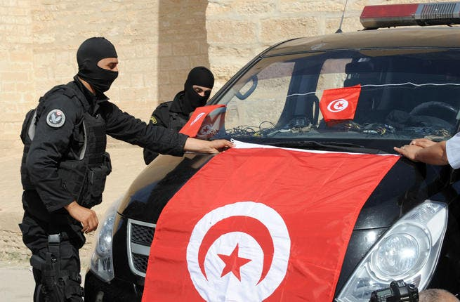 Tunisian Police Special Unit agents fix a national flag on their vehicle in front of the Okba Ibn Nafaa mosque in the central Tunisian city of Kairouan. (Fethi Belaid/ AFP)