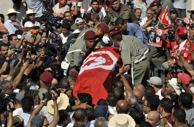 TUNISIA, Tunis : Tunisian soldiers load the coffin of assassinated opposition leader Mohamed Brahmi as his funeral procession takes place under military escort on July 27, 2013 in Tunis. AFP PHOTO / FETHI BELAID