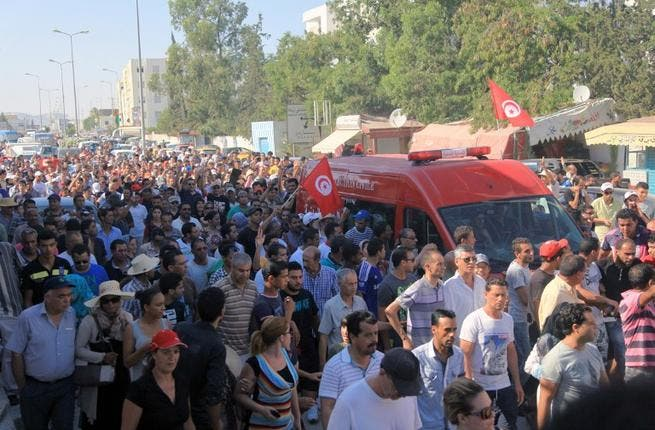 TUNISIA, Tunis : An ambulance, carrying the body of Tunisian opposition politician Mohamed Brahmi, drives to the Charles Nicile Hospital in Tunis before an autopsy after Brahmi was gunned down in front of his home on July 25, 2013. AFP PHOTO / FETHI BELAID
