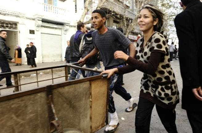 Residents run to take goods from a destroyed store. There were scenes of looting overnight in the suburbs of Tunis.