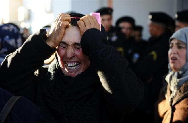 A woman cries in front of the prefecture as she waits with other people to meet the governor. Tunisian President Zine El Abidine Ben Ali described weekend rioting as