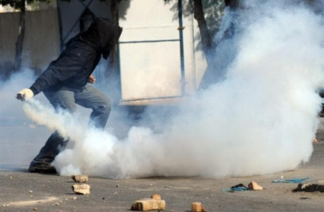 A Tunisian demonstrator prepares to throw a tear-gas canister during clashes with security forces.