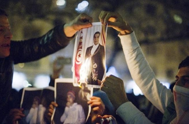 Men burn a picture of Tunisian President Zine El Abidine Ben Ali as they demonstrate against Ben Ali in Paris.