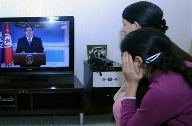A Tunisian family watches TV as Tunisian President Ben Ali gives his speech. Police opened fire on demonstrators in the centre of the Tunisian capital Thursday, killing at least one person, witnesses said.
