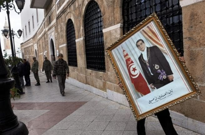 A Tunisian employee of the Prime ministry removes a portrait of former Tunisian president Ben Ali.